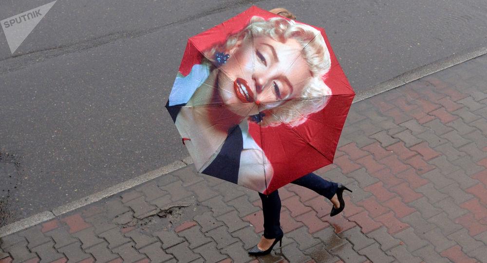 Женщина с зонтом на улице во время ливня, архивное фото