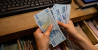 Сотрудник обменного пункта считает банкноты турецких лир, фото из архива