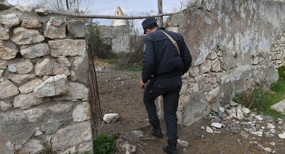 Азербайджанский полицейский у разрушенных домов в Карабахе, фото из архива