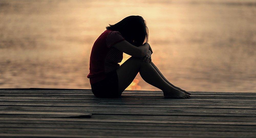 Девочка-подросток сидит в одиночестве, фото из архива