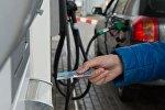 Мужчина расплачивается кредитной картой на автозаправочной станции, фото из архива