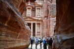 Туристы осматривают скальный храм-мавзолей Эль-Хазне в древнем городе Петра в Иордании