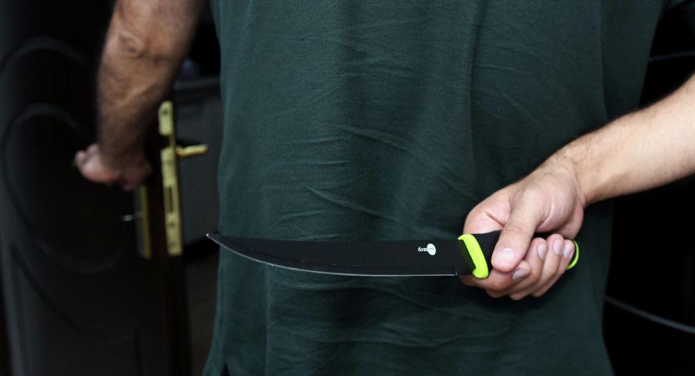 Мужчина, держащий нож за спиной, фото из архива