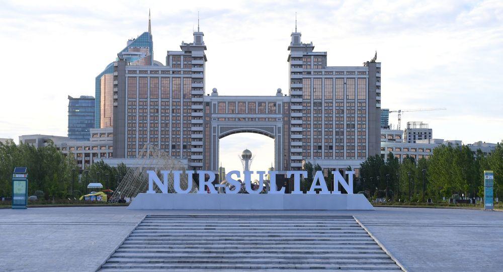 Надпись Nursultan в парке Гашиктар на фоне здания Национальной компании КазМунайГаз в Нур-Султане