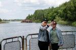 Туристы делают селфи в речном порту заброшенного города Припять. Вокруг — буйная растительность