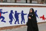 Иранская женщин на фоне граффити у бывшего здания посольства США в Тегеране, фото из архива