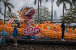 Мальчик в маске позирует для фотографии с изображением дракона в первый день Лунного Нового года в Гонконге