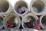 Рабочие-мигранты отдыхают в цементных трубах в Индии