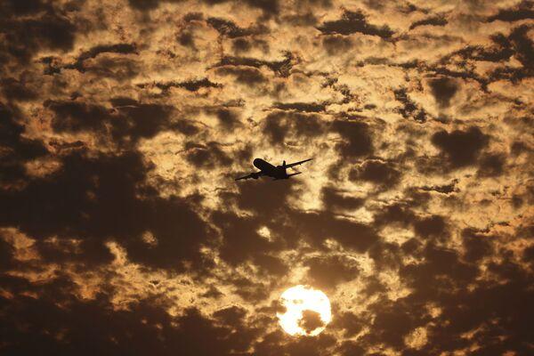 Силуэт самолета на фоне пылающих в заходящем солнце облаков в Ахмедабаде, Индия - Sputnik Азербайджан