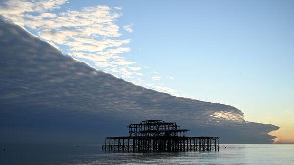 Облака, напоминающие огромную волну, над пляжем в Брайтоне на юге Англии - Sputnik Азербайджан