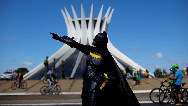 Участник протестов в костюме Бэтмена в Бразилии - Sputnik Азербайджан