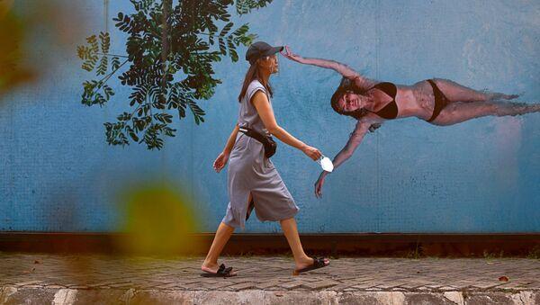 Девушка в защитной маске на фоне граффити с изображением девушки в купальнике в Джакарте, Индонезия - Sputnik Азербайджан