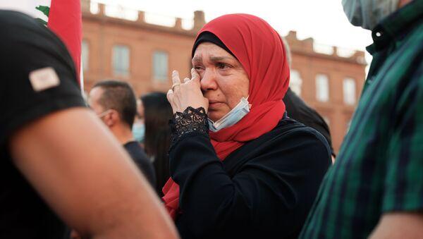 Женщина плачет на собрании в Тулузе, Франция, в поддержку пострадавших от взрыва в Бейруте - Sputnik Азербайджан