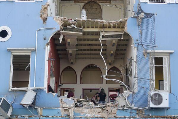 Жители осматривают повреждения своего дома в районе с видом на разрушенный порт Бейрута - Sputnik Азербайджан