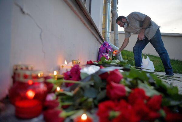 Мужчина возлагает цветы к посольству Ливана в Москве в память о жертвах взрыва - Sputnik Азербайджан