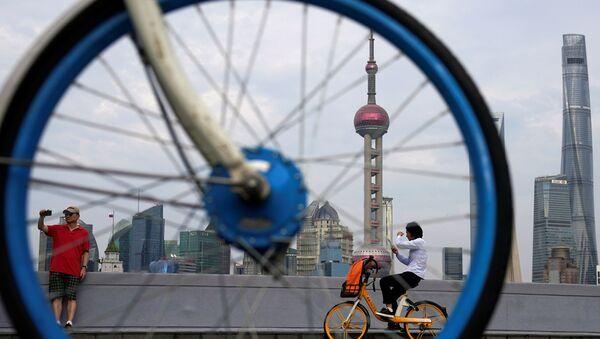 Люди на велосипедах у финансового района Луцзяцзуй в Шанхае  - Sputnik Азербайджан