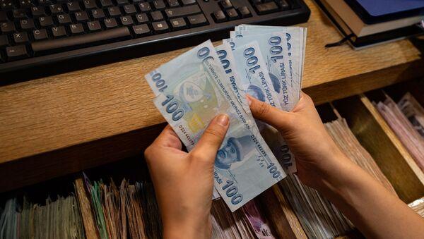 Сотрудник пункта обмена валюты считает банкноты турецких лир, фото из архива - Sputnik Азербайджан