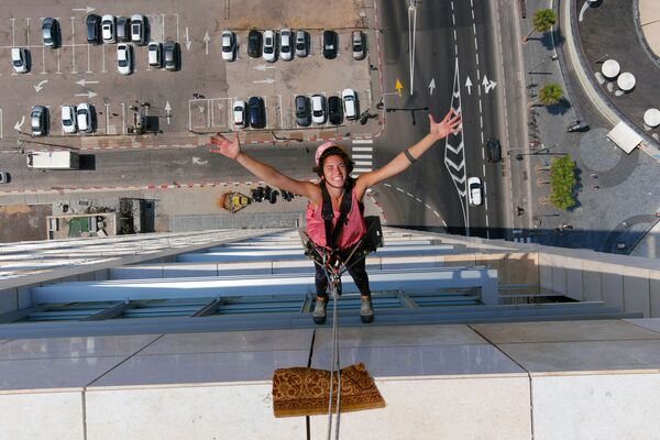 Специалист по мойке окон Ноа Толедо во время работы на высотном здании в Тель-Авиве, Израиль - Sputnik Азербайджан