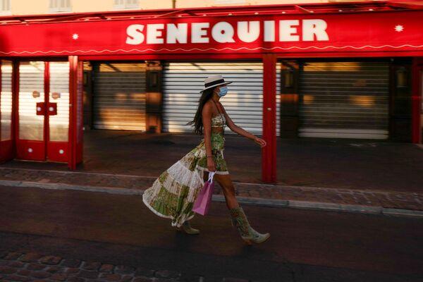 Девушка в защитной маске у закрытого кафе Le Cafe Senequier на набережной в Сен-Тропе, Франция - Sputnik Азербайджан