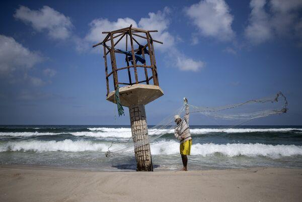 Палестинский рыбак чистит свою рыболовную сеть - Sputnik Азербайджан