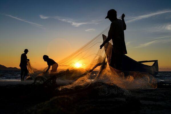 Рыбаки чистят сети после рыбалки на закате в Банда-Ачех, Суматра, Индонезия - Sputnik Азербайджан