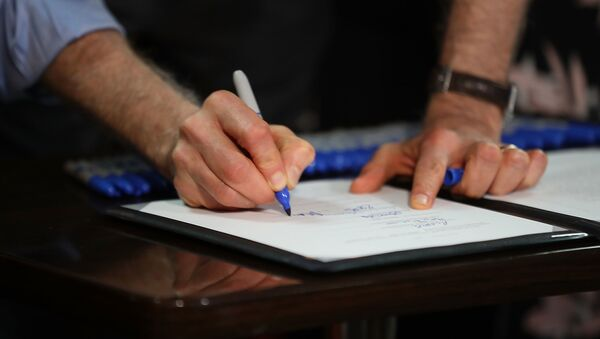 Мужчина ставит подпись на документе, фото из архива - Sputnik Азербайджан
