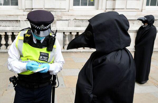 Полицейский и активист Extinction Rebellion во время акции протеста в Лондоне, Великобритания - Sputnik Азербайджан