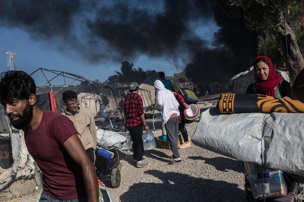 Мигранты на территории сгоревшего лагеря для мигрантов Мориа в Греции - Sputnik Азербайджан