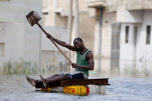 Житель на самодельном плоту с лопатой плывет по затопленным после проливных дождей улицам в Кеур-Массаре, Сенегал - Sputnik Азербайджан