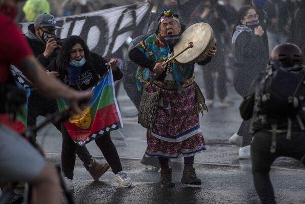 Женщина из числа коренного населения мапуче во время акции протеста против действий правительства в связи с пандемией коронавируса в Сантьяго - Sputnik Азербайджан