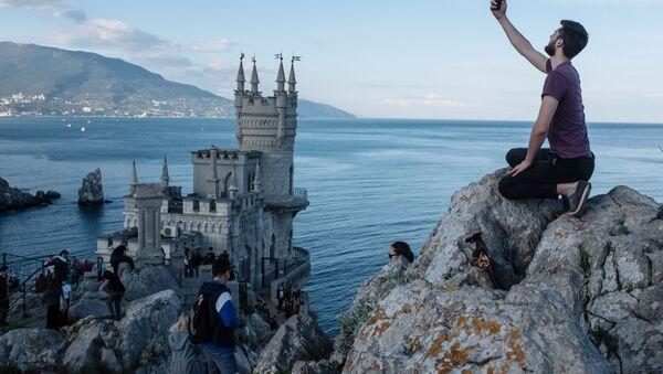 Люди на береговой скале рядом с замком Ласточкино гнездо в поселке Гаспра в Крыму, фото из архива - Sputnik Азербайджан
