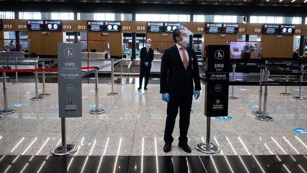 Сотрудники в защитных масках ждут обслуживания пассажиров в аэропорту Стамбула, фото из архива - Sputnik Азербайджан