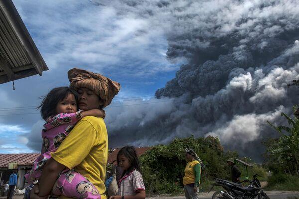 Местные жители в деревне у подножия действующего вулкана Синабунг в провинции Северная Суматра в Индонезии - Sputnik Азербайджан