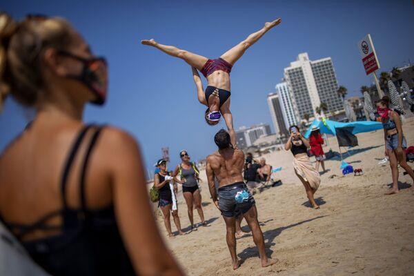 Акробаты выступают во время акции протеста против решения правительства закрыть пляжи из-за пандемии коронавируса в Тель-Авиве, Израиль - Sputnik Азербайджан