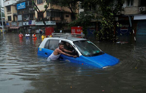 Мужчина толкает такси по затопленной улице после ливня в Мумбаи, Индия - Sputnik Азербайджан
