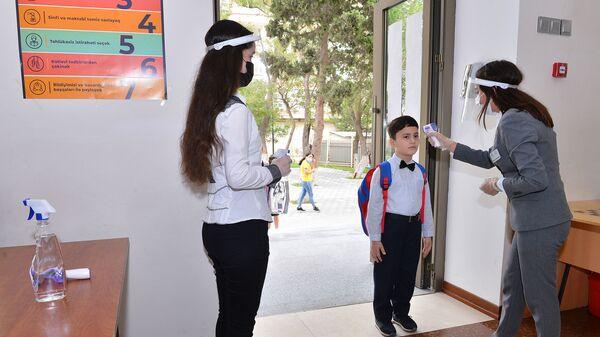 Bakıda məktəbin girişində şagirdin temperaturu ölçülür, arxiv şəkli - Sputnik Azərbaycan