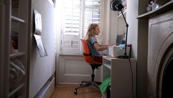 Пандемия коронавируса COVID-19. Дистанционное обучение. Девочка сидит за компьютером в доме в Бруклине, США - Sputnik Азербайджан