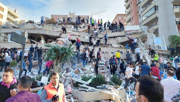 Местные жители и официальные лица ищут выживших в обрушившемся здании после сильного землетрясения в Измире  - Sputnik Azərbaycan