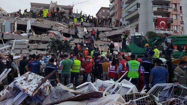 Местные жители и официальные лица ищут выживших в обрушившемся здании после сильного землетрясения в Измире  - Sputnik Азербайджан