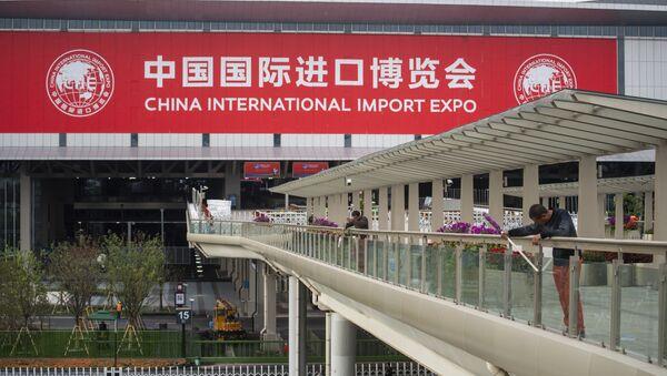 Рабочие перед Национальным выставочным и конференц-центром (Шанхай), главным местом проведения Китайской международной импортной выставки (CIIE) - Sputnik Азербайджан