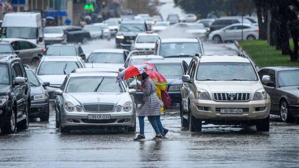 Bakıda yağışlı havada yol keçən piyadalar, arxiv şəkli - Sputnik Azərbaycan