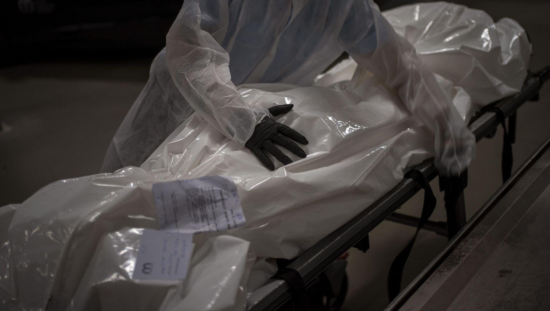 Работник похоронного бюро перемещает тело человека, умершего от COVID-19, в морг  - Sputnik Азербайджан, 1920, 15.03.2021