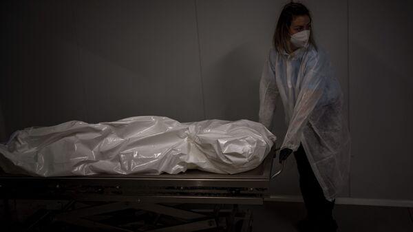 Работник похоронного бюро перемещает тело человека, умершего от COVID-19, в морг  - Sputnik Азербайджан
