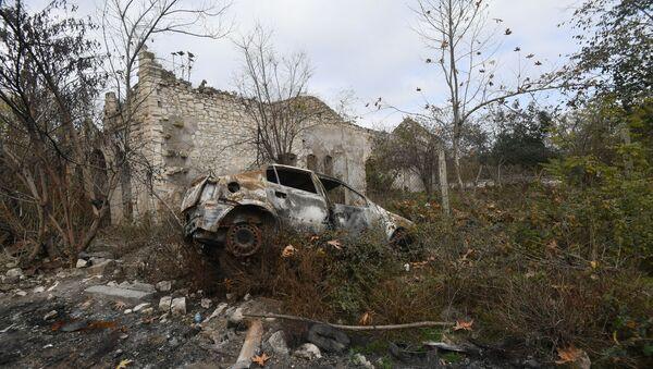 Füzulidə dağılmış binanın qarşısında yanmış avtomobil - Sputnik Азербайджан