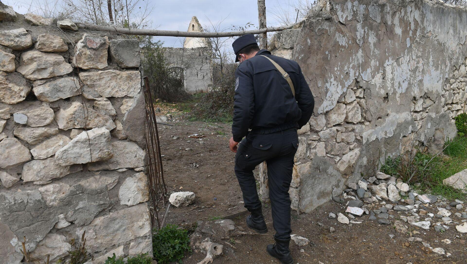 Азербайджанский полицейский у разрушенных домов в Карабахе, фото из архива - Sputnik Азербайджан, 1920, 08.03.2021