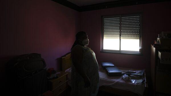 Женщина в медицинской маске дома, фото из архива - Sputnik Азербайджан