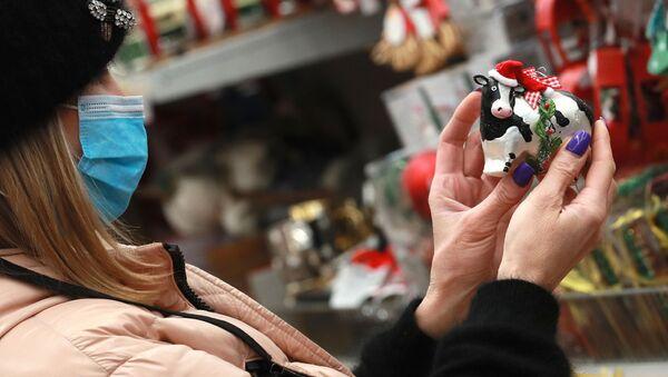 Покупательница выбирает сувенир в магазине перед Новым годом - Sputnik Азербайджан