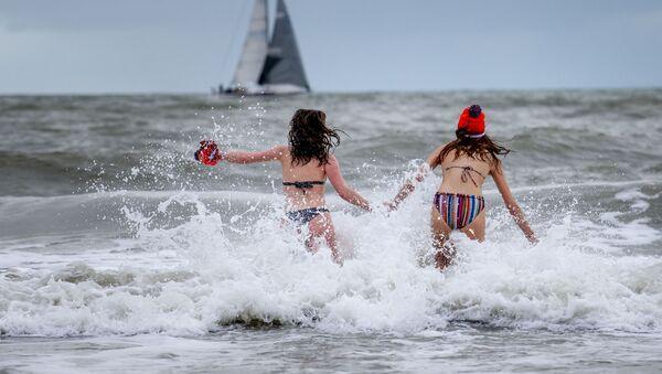 Девушки забегают в море в Схевенингене, Нидерланды - Sputnik Azərbaycan