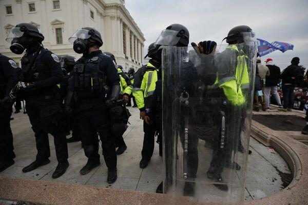 Сотрудники полиции во время акции протеста сторонников действующего президента США Дональда Трампа у здания конгресса в Вашингтоне - Sputnik Азербайджан