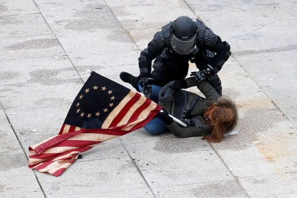 Полицейский задерживает протестующего у здания Конгресса в Вашингтоне - Sputnik Азербайджан